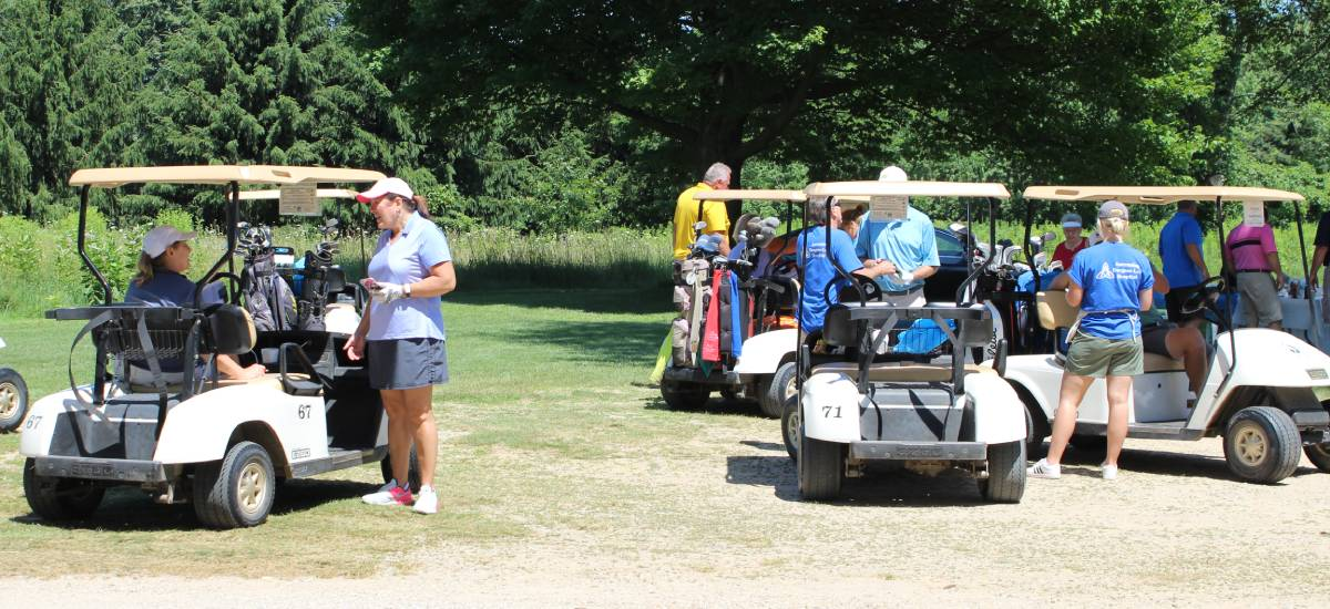 Group of people standing around golf carts.